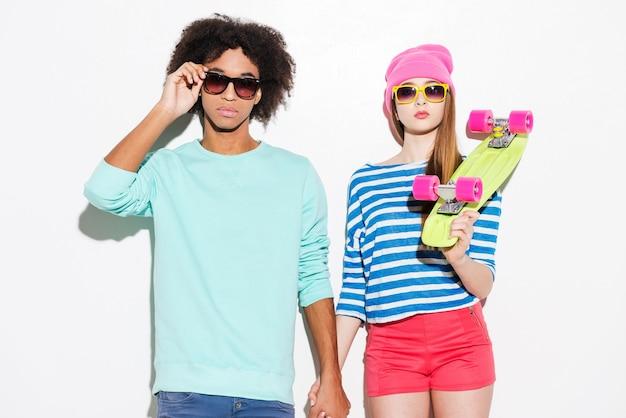 Super style et amoureux. funky jeune couple portant des lunettes et posant sur fond blanc