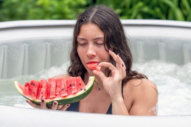 Superbe adolescente aux cheveux longs et noirs et pastèque dans la piscine gonflable du jardin