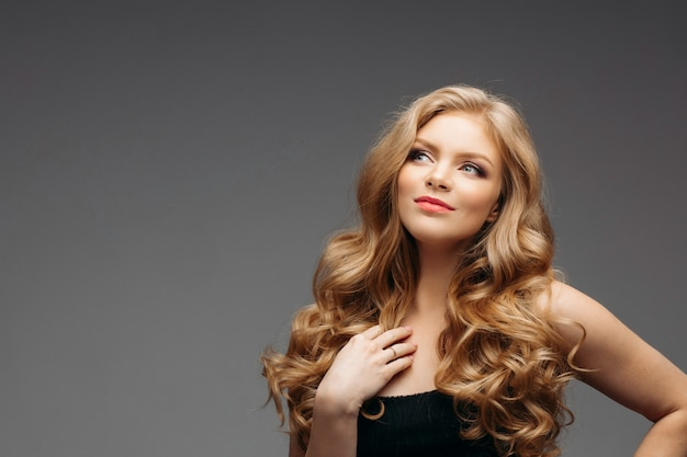 Superbe beauté naturelle aux cheveux blonds ondulés.