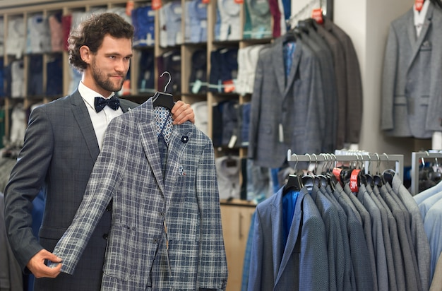 Superbe bel homme debout en magasin avec une veste grise.