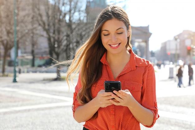 Superbe belle jeune femme aux cheveux longs, messagerie sur le téléphone intelligent dans la rue de la ville.