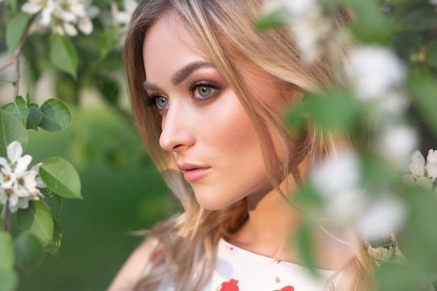 Superbe blonde souriante dans un jardin de fleurs de pommier au soleil