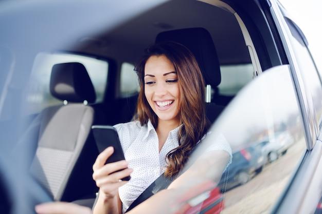 Superbe brune caucasienne souriante brune assise dans sa voiture avec ceinture de sécurité et à l'aide de téléphone intelligent pour envoyer des sms.