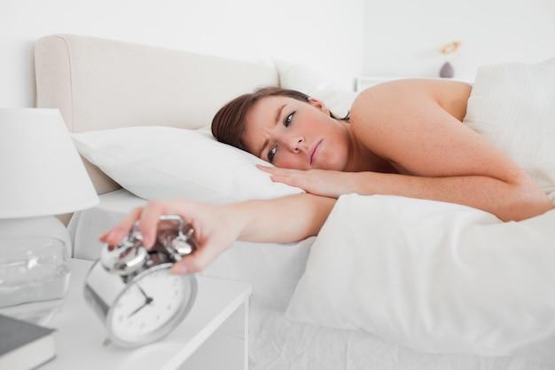 Superbe brune femme se réveiller avec une horloge en position couchée