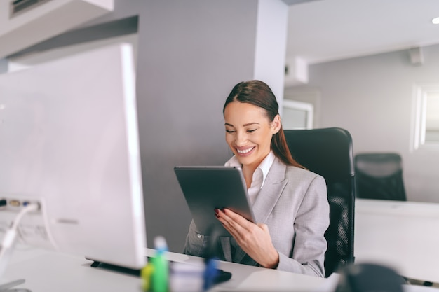 Superbe brune avec un grand sourire à pleines dents vêtue de vêtements de cérémonie assis au bureau et à l'aide de tablette