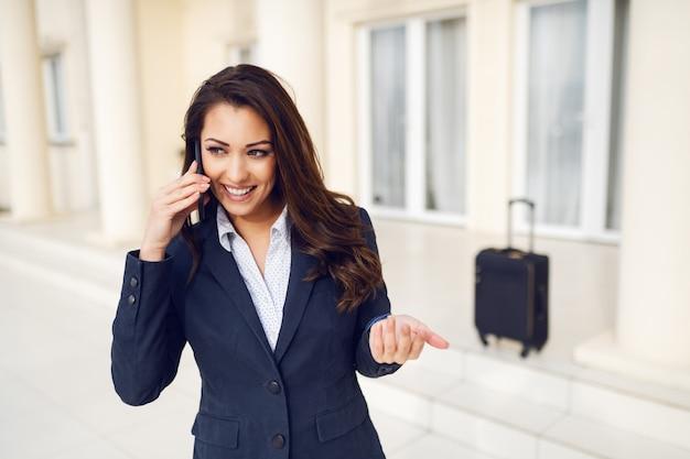 Superbe brune souriante habillée décontractée intelligente à l'extérieur et à l'aide d'un téléphone intelligent pour appeler un taxi. en arrière-plan, ses bagages. concept de voyage d'affaires.