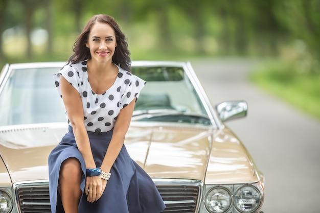 Superbe brune sourit à la caméra assise sur le capot avant d'une voiture décapotable d'époque au bord de la route dans la nature.