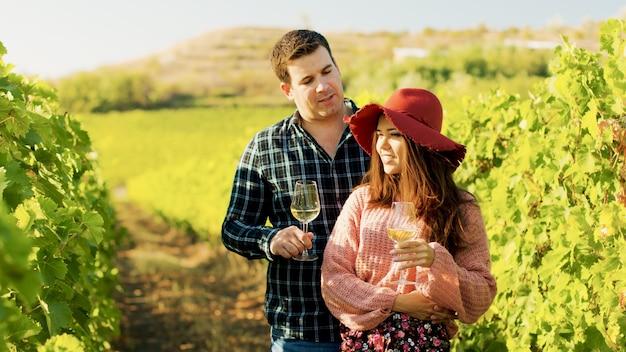 Superbe couple s'embrassant tout en tenant des verres de vin dans les mains.