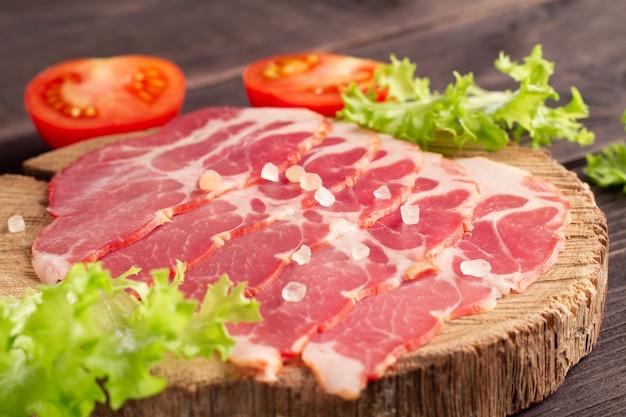 Superbe délicieuse tranche de jamon sur une assiette en bois avec des légumes verts, des tomates et du sel