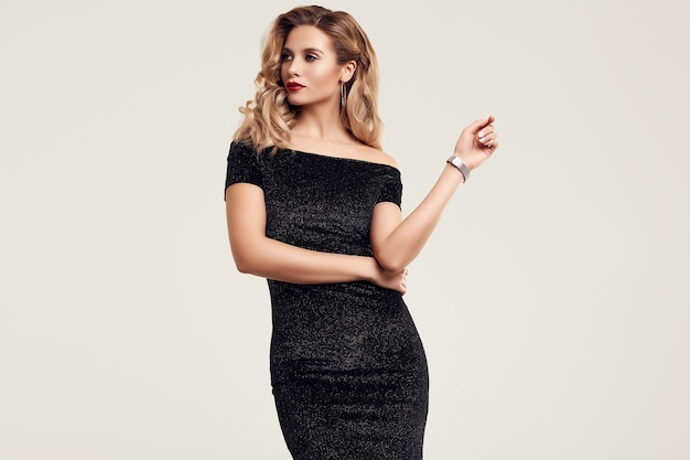 Superbe élégante femme blonde sensuelle vêtue d'une robe noire fashion