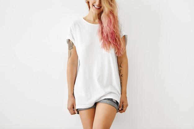 Superbe élégante jeune femme de race blanche avec des tatouages sur les bras et des cheveux longs rosâtres souriant largement posant au mur blanc, vêtue d'un t-shirt blanc blanc et d'un short en jean