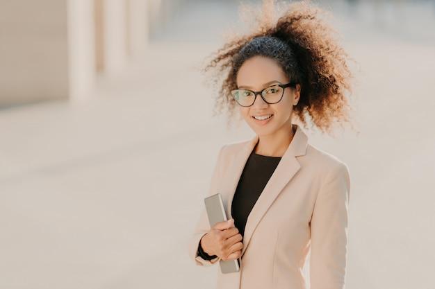 Superbe femme d'affaires afro-américaine positive se promène en plein air avec pavé tactile