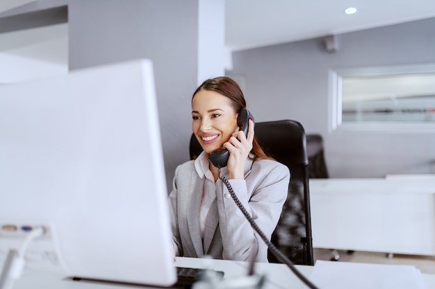 Superbe femme d'affaires de race blanche aux longs cheveux bruns et en tenue de soirée à l'aide d'un ordinateur