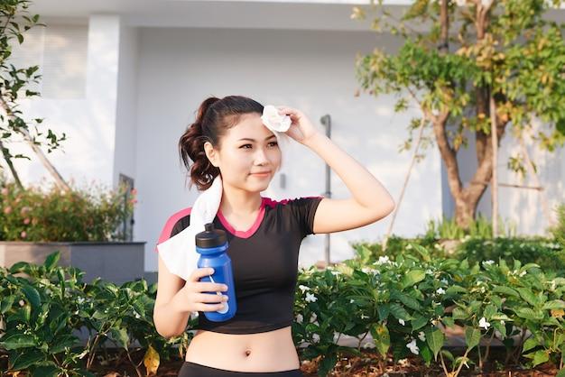 Superbe femme asiatique de remise en forme essuyant la sueur et tenant une bouteille d'eau après avoir fait du jogging ou couru à l'extérieur