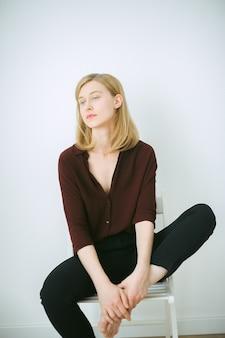 Superbe femme assise sur une chaise dans la chambre avec un fond blanc en chemise marron et pantalon noir.