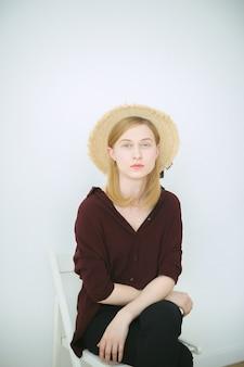 Superbe femme assise et regardant en chemise brune, pantalon noir et chapeau de soleil dans la chambre avec un fond blanc.