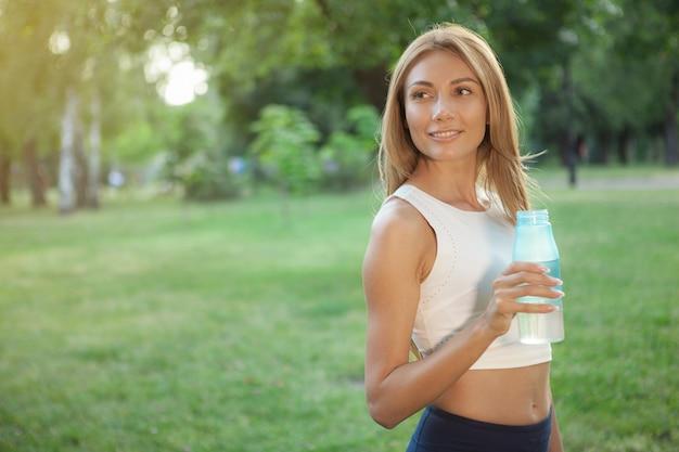 Superbe femme athlétique buvant de l'eau dans le parc