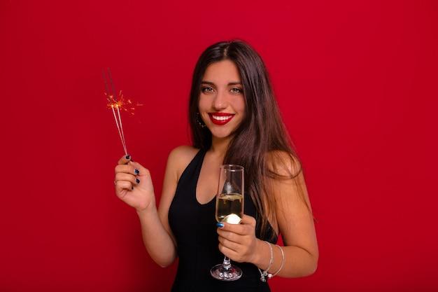 Superbe femme aux cheveux longs noirs portant une robe noire avec des épaules nues tenant un verre de champagne et sparkler se préparant pour la fête de noël sur le mur rouge