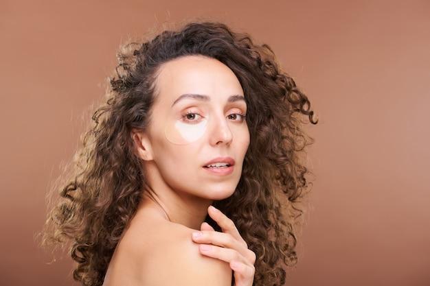 Superbe femme aux cheveux noirs et bouclés avec des taches rajeunissantes sous les yeux touchant l'épaule nue