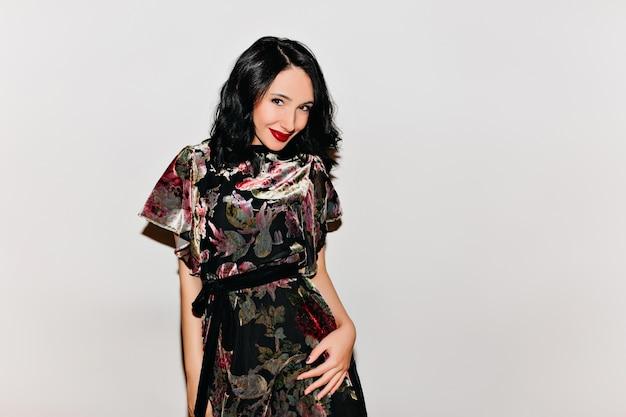 Superbe femme aux cheveux noirs debout sur un mur lumineux avec sourire
