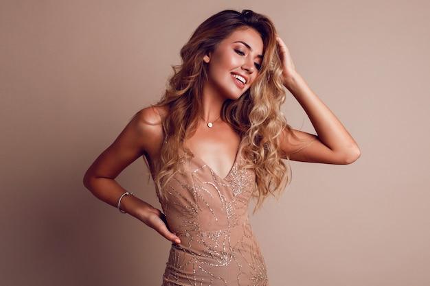 Superbe femme aux cheveux ondulés blonds portant une élégante robe beige