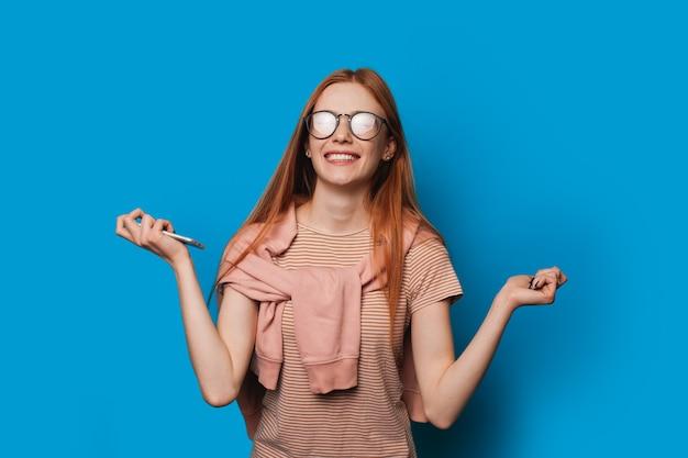 Superbe femme aux cheveux rouges et taches de rousseur tient un mobile et regarde à travers des lunettes tout en faisant signe au gagnant sur un fond bleu