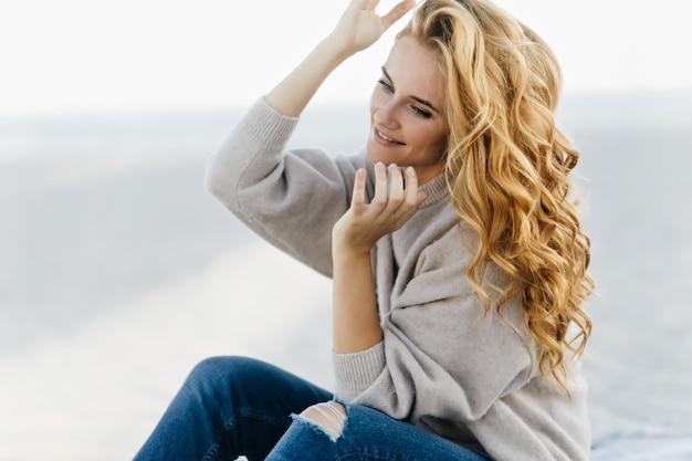 Superbe femme aveugle aux cheveux linges se reposant sur la plage dans la froide matinée. heureux modèle féminin élégant posant dans la nature