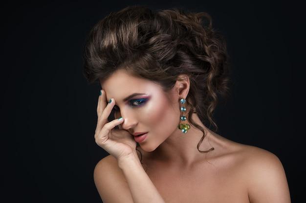 Superbe femme avec une belle coiffure et des boucles d'oreilles brillantes