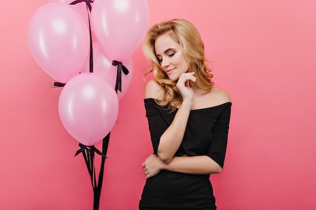 Superbe femme blanche posant sur un mur rose avec un sourire fatigué. enthousiaste modèle féminin caucasien debout à côté de ballons de fête rose.