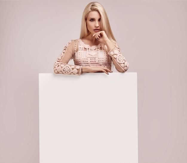 Superbe femme blonde tenant un panneau vierge