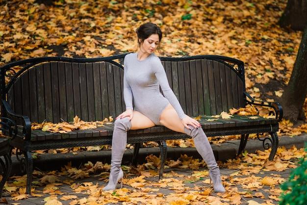 Superbe femme brune dans un body, lingerie et manteau marchant dans le parc