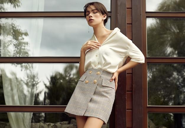 Superbe femme brune en jupe et blouse blanche
