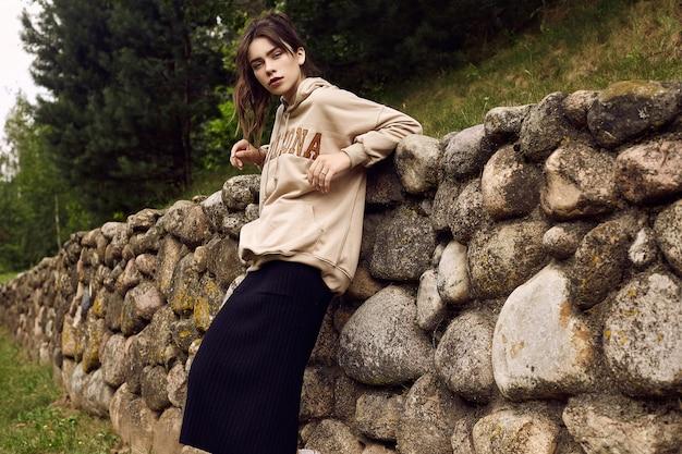 Superbe femme brune à la mode à capuche dans l'allée du jardin