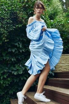 Superbe femme brune à la mode robe bleue dans le jardin