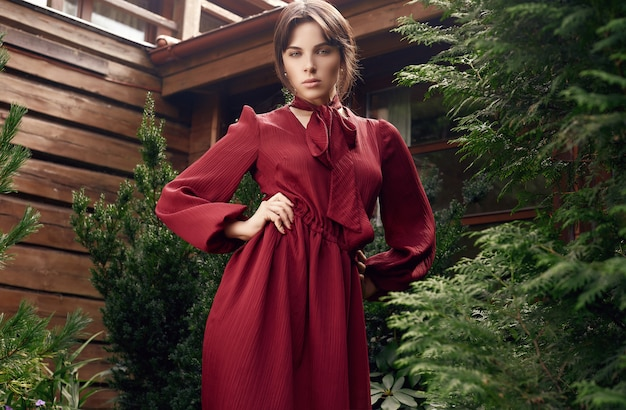 Superbe femme brune à la mode robe rouge dans le jardin