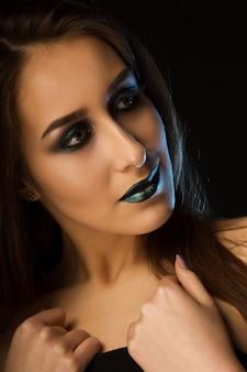Superbe femme brune avec une peau parfaite et un maquillage vert métallique créatif. closeup portrait en studio sur fond sombre
