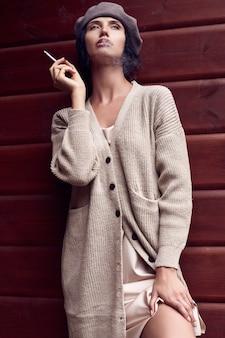 Superbe femme brune en robe classique de mode avec cigarette