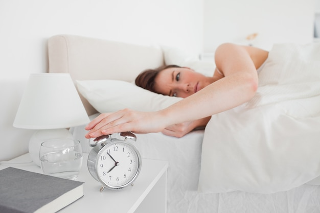 Superbe femme brune se réveiller avec une horloge en position couchée