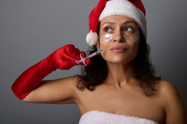 Une superbe femme brune en tenue de carnaval de santa tient une seringue sur son pli nasogénien et lève les yeux sur l'espace de copie pour faire de la publicité pour les cadeaux de noël pour les salons de spa. concept de cosmétologie d'injection