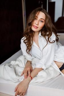 Superbe femme en chemisier blanc enjoing matin au lit.