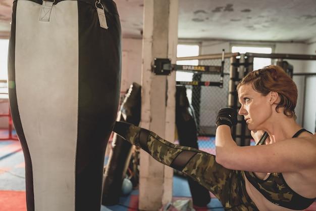 Superbe femme, combattant mma dans la salle de gym pendant l'entraînement. se préparer pour un match en cage dure