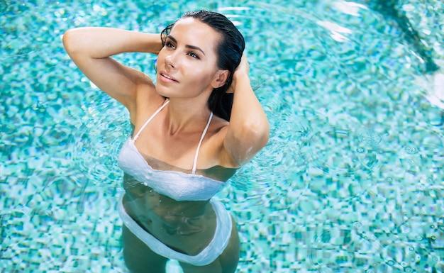 Superbe femme élégante en bikini blanc avec un corps mince bronzé pose dans la piscine.