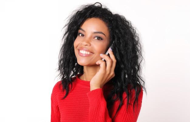 Superbe femme ethnique africaine dans un pull rouge tricoté regarde le coin supérieur gauche et rit tout en parlant sur son smartphone