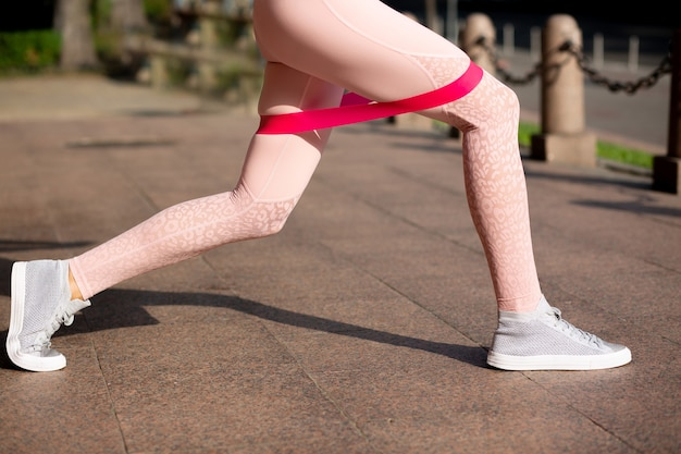 Superbe femme en forme faisant de l'exercice pour les jambes avec une bande de résistance élastique dans le parc
