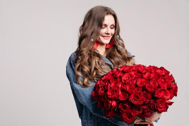Superbe femme avec de grandes boucles d'oreilles tenant des roses et souriant