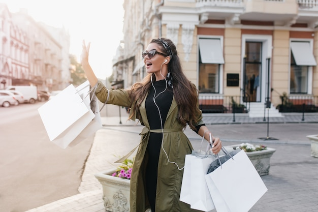 Superbe femme hispanique dans des écouteurs blancs en agitant la main à quelqu'un debout dans la rue avec des paquets