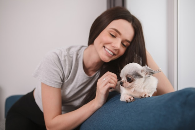 Superbe femme joyeuse caressant son adorable petit chien, restant à la maison