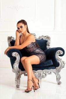 Superbe femme luxueuse en robe de mode assise sur un canapé. boutique de mode pour femmes.