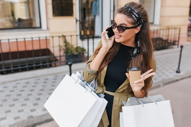 Superbe femme à la mode aux cheveux noirs parlant au téléphone en journée ensoleillée transportant de gros paquets de boutique