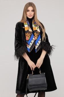 Superbe femme à la mode en manteau de fourrure avec sac à main.